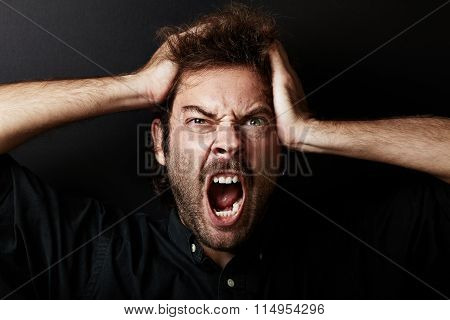 Portrait of young guy who grabs his head in hands, stress. Horizontal.