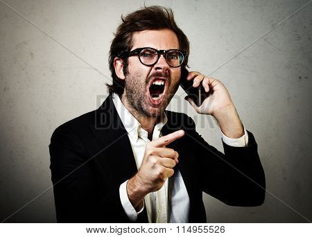 Portrait of young man wearing trendy suit and furiously screaming on the smartphone. Horizontal