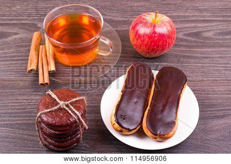 Tea with cinnamon, cakes eclairs, apple