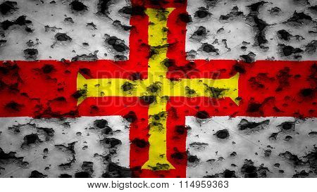 Flag of Guernsey painted on wall with bullet holes