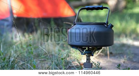Close-up image of burning gas stove and kettle