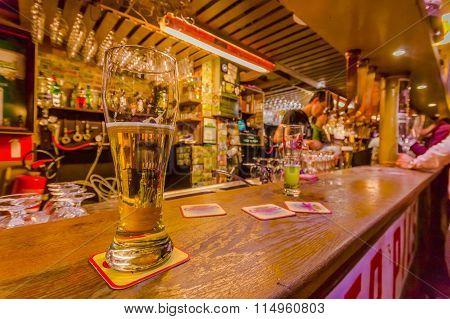 BRUSSELS, BELGIUM - 11 AUGUST, 2015: Glass beer sitting on bar counter inside Delirium Bar, selectio