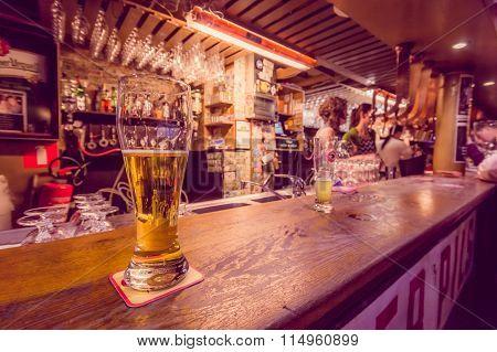 BRUSSELS, BELGIUM - 11 AUGUST, 2015: Beer glass sitting on bar counter inside Delirium Bar, selectio