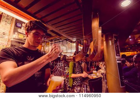 BRUSSELS, BELGIUM - 11 AUGUST, 2015: Bartender at Delirium Bar tapping beer into tall glass with sev