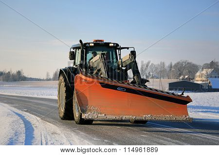 Tractor And Snow Plow On The Road