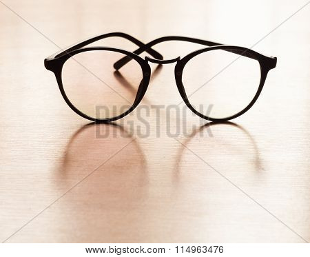 Eyeglasses With Reflection On Wooden Table