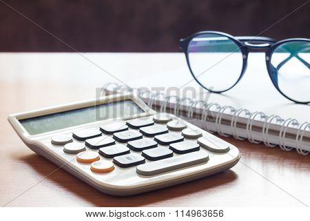 Calculator With Eyeglasses On Wooden Table