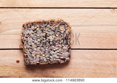 Wholemeal, wholewheat slice of bread on wooden table. Organic, healthy food, breakfast.