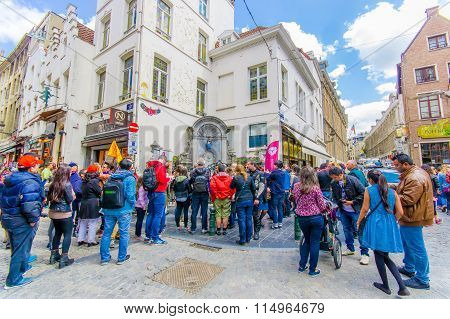 BRUSSELS, BELGIUM - 11 AUGUST, 2015: Crowd of tourists watching Manneken Pis famous landmark bronze