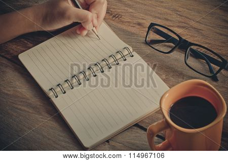 Hand Left Writing On Notebook And Coffee Cup On A Wooden Table.