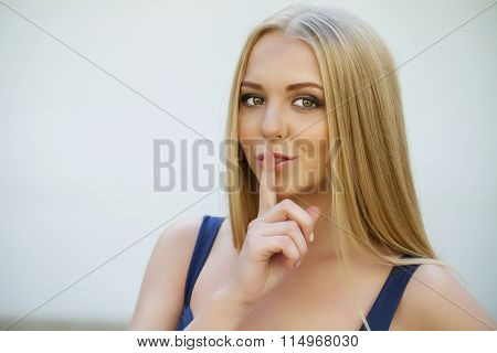 Young beautiful haired woman has put forefinger to lips as sign of silence