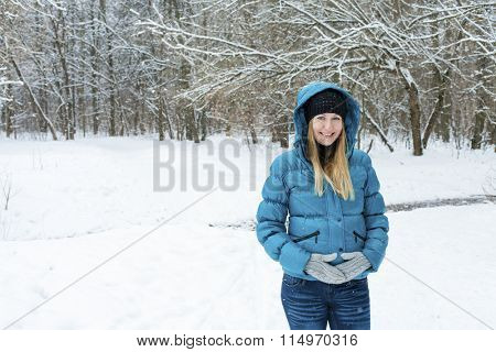 Portrait of a beautiful young woman in a turquoise feather bed and a knitted cap on a background of a winter park