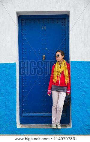 One Asian Woman Stands In Front Of Navy Metal Door