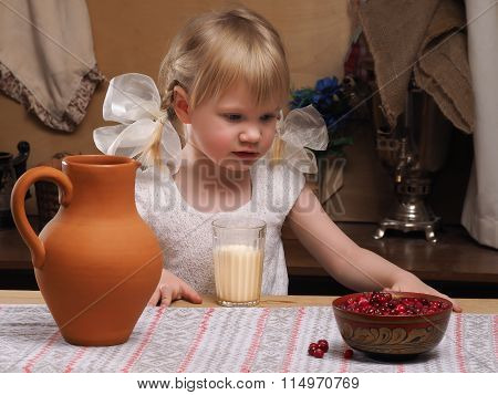 The child looks at and holds a berry cranberries in hand