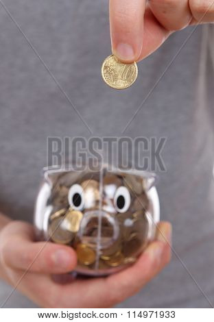 Male hand putting coin into a piggy bank. focus specifically on the coin.