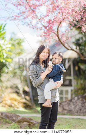Asian Mother Holding Baby In The Blooming  Cherry Blossom Garden.