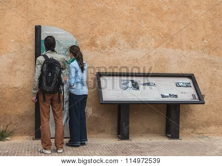 Two Tourist Read Guiding Map Of Kasbah Of The Udayas