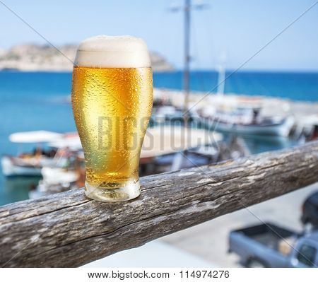 Glass of light beer on the  seaside bar counter.