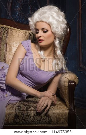 Woman In Historic Baroque Style Dress And White Wig  On The Couch