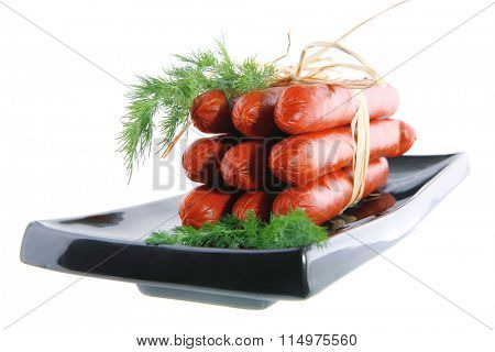 smoked sausages served on a black plate over white