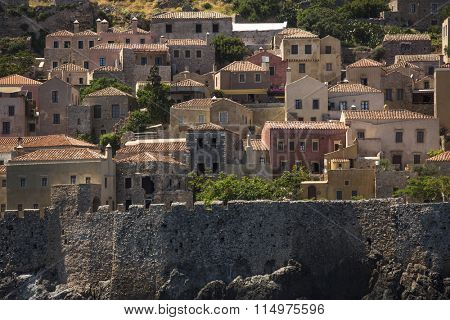 MONEMVASIA, GREECE - CIRCA MAY, 2014: View of stone houses at Medieval fortress. Mainland and the rock on which the city is located, connected by a highway bridge in 1971.