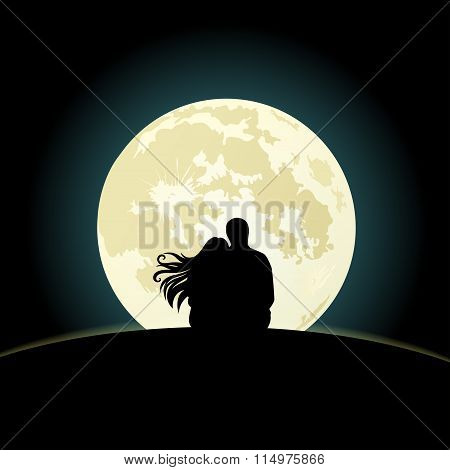 Couple on a hill sitting under the moonlight