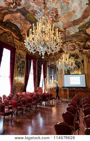 VENICE - AUGUST 27: Interior of Aula Magna Silvio Trentin Room in Palazzo Dolfin - Ornate Room Decorated with Tiepolo Fresco Paintings, Elaborate Chandelier and Red Chairs. August 27, 2015 in Venice