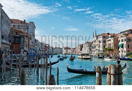 VENICE - AUGUST 27: Boat traffic on the Grand Canal, Venice, with gondolas, private craft and a vaporetto or water bus passing old historical palazzo lining the waterway. August 27, 2015 in Venice