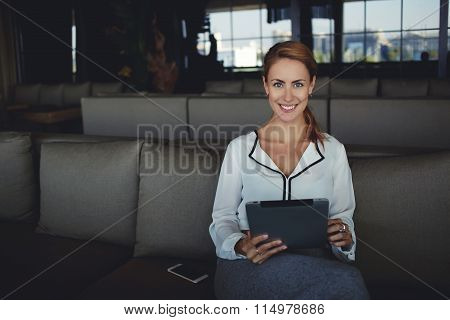 Beautiful smiling woman looking at camera while sitting with touch pad in modern coffee shop