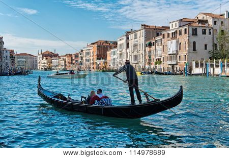 VENICE - AUGUST 27: Gondolier rowing tourists in his gondola on the Grand Canal in Venice past ancient historic palazzo with private boats in the background. August 27, 2015 in Venice