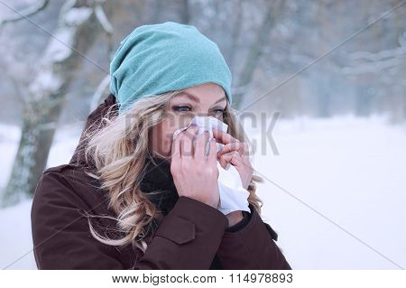 woman blowing her nose in winter