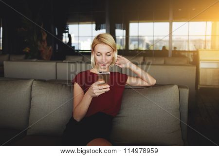 European woman searching information on cell telephone while sitting in restaurant interior
