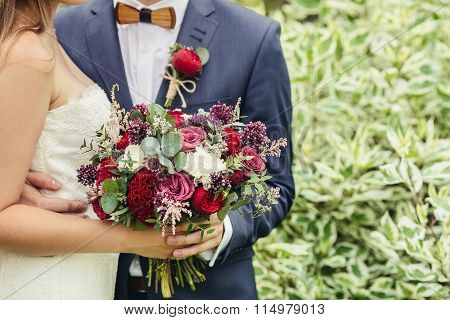 Groom With Wooden Bow-tie And Red Boutonniere Hug Bride With Lilac Wedding Bouquet