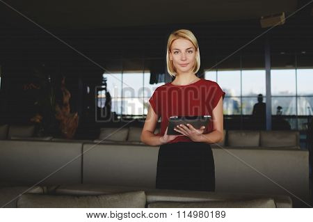 Successful female CEO dressed in elegant clothes posing while work on portable netbook
