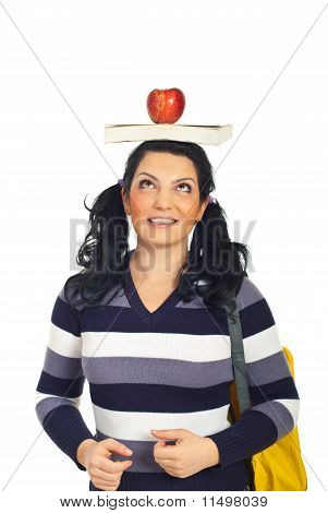 Mulher alegre estudante com livro na cabeça