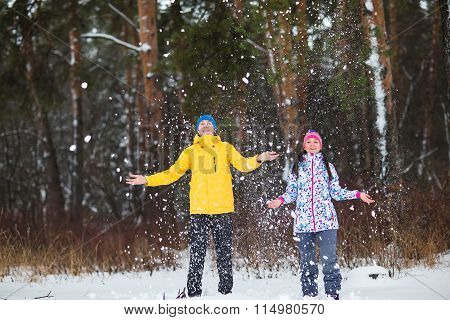 Young Couple In The Winter Woods.