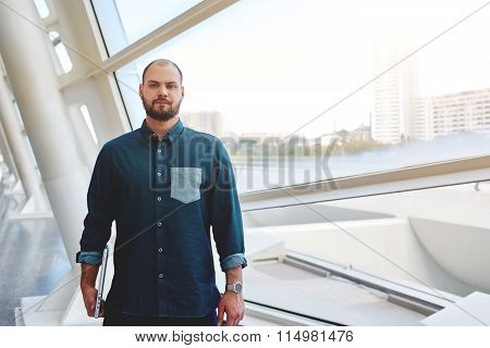 Successful businessman with laptop computer in hand posing near window with city view