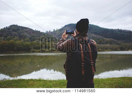 Stylish hipster guy with a rucksack on his back taking photo on cell telephone