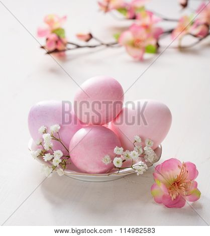Plate  with pink   Easter eggs  and artificial flowers  on wooden table. Focus on the  Easter eggs