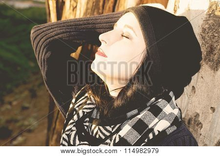 Beautiful woman relaxing in woodland standing leaning against the trunk if a tree with her eyes clos