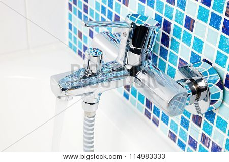 Single handle wall mount chrome bathroom faucet with running water on a blue mosaic wall