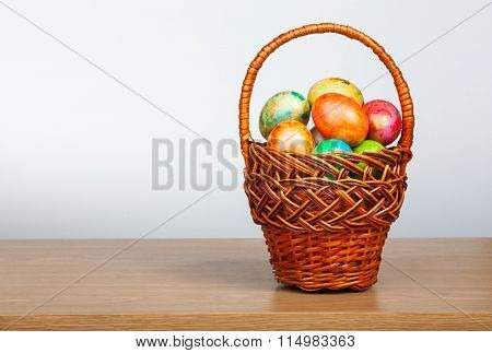 Colored easter eggs in a wicker basket on a table