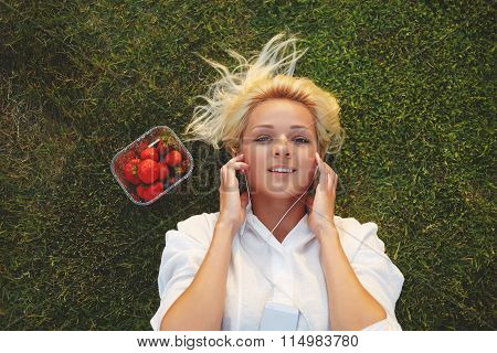 Attractive female enjoying music while resting on the green grass after strolling