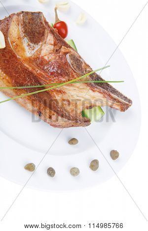 fresh hot roasted beef meat bone steak on ceramic dish with red hot pepper and capers isolated  over white background