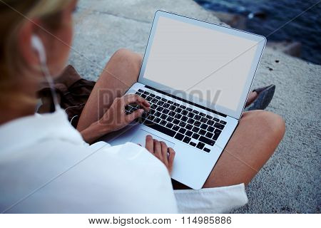 Hipster gir tourist chatting on laptop computer outside