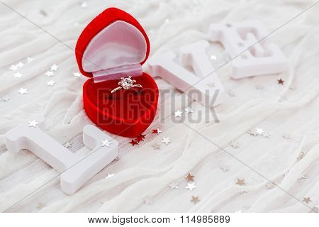 Word Love On White Fabric Background With Engagement Diamond Ring In Red Gift Box.