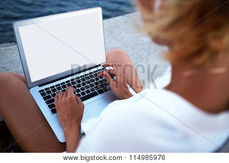 Female student chatting on laptop computer while sitting outside near sea