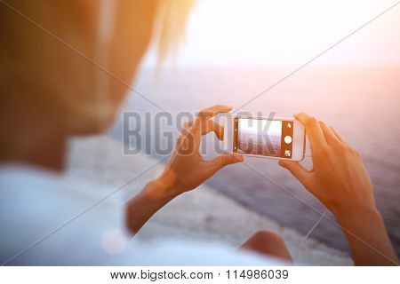 Woman taking picture of ocean landscape on her mobile phone while standing on the beach