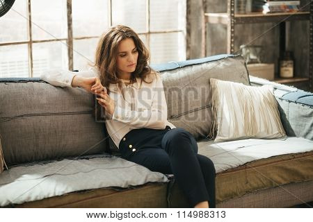 Thoughtful Young Woman Is Sitting On Sofa In Loft Living Room