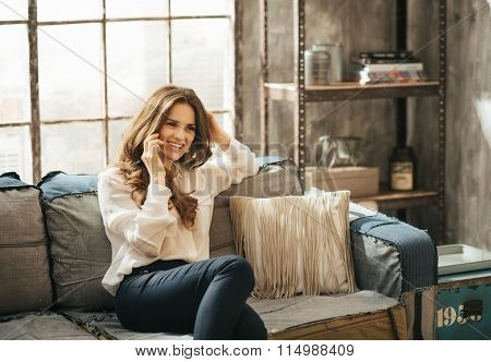 Smiling Stylish Woman Sitting On Divan And Talking Smartphone